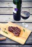 BBQ steak. Barbecue grilled beef steak meat with red wine Royalty Free Stock Photo