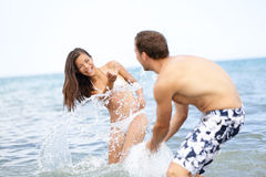 Beach summer fun couple playful splashing water Stock Photo