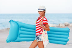 Beach woman happy and wearing beach hat with blue mattress having summer fun during travel holidays vacation Royalty Free Stock Photos