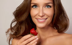 Beatiful girl with Perfect smile eat red strawberry  white teeth and healthy food Stock Images