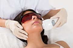 Beautician giving epilation laser treatment Royalty Free Stock Photography