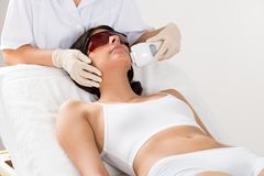 Beautician giving epilation laser treatment Royalty Free Stock Images