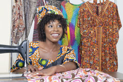 Beautiful African American female tailor looking away while stitching cloth on sewing machine Royalty Free Stock Image