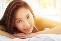 Beautiful asian woman relaxing on the bed with sunlight ba Royalty Free Stock Photos