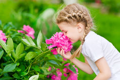 Beautiful blond little girl with long hair smelling flower Stock Photos