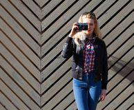 Beautiful blonde girl in huge sunglasses and a black jacket posing nex to wooden wall sunny day makes shoot vintage camera Stock Photo