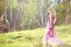 Beautiful blonde girl in pink long dress on a background of nature Stock Photo
