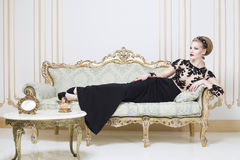 Beautiful blonde royal woman laying on a retro sofa in gorgeous luxury dress Stock Image