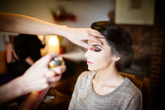 Beautiful bride doing her hair and makeup. Hairstylist spraying hairspray on her updo Royalty Free Stock Images