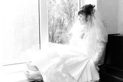 Beautiful Bride sad, waiting by the window Stock Photo