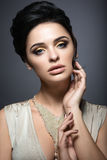 Beautiful brunette woman with perfect skin, gold makeup and handmade jewelry. Beauty face. Royalty Free Stock Images