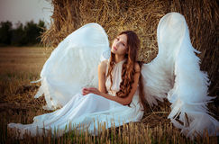 Beautiful girl with angel wings is sitting front of the hay Stock Photos