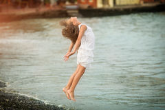 Beautiful girl jumping through the waves Royalty Free Stock Image