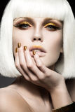 Beautiful girl in a white wig, with gold makeup and nails. Celebratory image. Beauty face. Stock Images