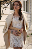 Beautiful ladylike woman in elegant wool coat and lace dress Stock Photos