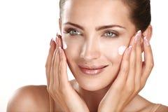 Beautiful model applying cosmetic cream treatmen on her face Royalty Free Stock Photo