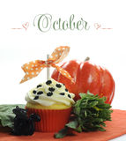 Beautiful orange Halloween theme cupcake with seasonal flowers and decorations for the month of October Stock Photo