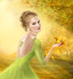 Beautiful romantic woman and fantasy gold bird Stock Photo