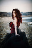 Beautiful sad goth girl standing on sea shore. Rear view Stock Photos