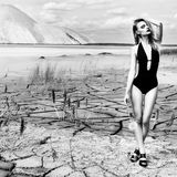 Beautiful sexy cute girl in a fashion shoot in a bathing suit in desert dry cracked earth in the background of the mountains Stock Photo