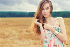 Beautiful sexy romantic girl with red hair wearing a colored dress, the wind standing in the field on a cloudy summer day Stock Photo