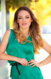 Beautiful sexy woman with green dress and blond hair outdoor. Fashion girl Stock Image