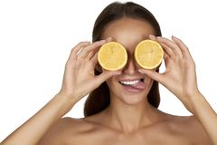 Beautiful sexy young woman with perfect healthy skin and long brown hair day makeup bare shoulders holding orange lemon grapefruit Royalty Free Stock Image