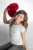 Teen girl with heart shaped pillow Stock Photo