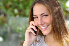 Beautiful woman with a perfect white smile talking on the mobile phone Stock Photo
