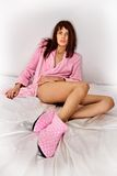 Beautiful woman in pink cosy sleepwear on the bed. Royalty Free Stock Photography