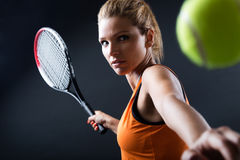 Beautiful woman playing tennis indoor. Isolated on black. Royalty Free Stock Image
