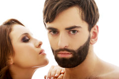 Beautiful woman whispering to man's ear. Royalty Free Stock Photography