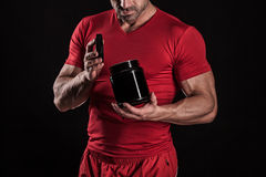 Beautiful young athletic man holding a jar of sports nutrition Royalty Free Stock Images