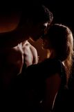 Beautiful young couple hugging and kissing isolated on black background. Royalty Free Stock Photos