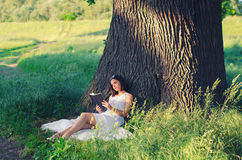 Beautiful young girl reading book while sitting under giant oak Stock Photography