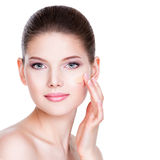Beautiful young woman with cosmetic foundation on a skin. Royalty Free Stock Photos