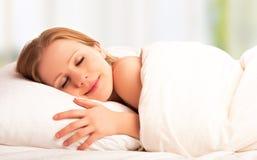 Bei sonno e sorrisi della donna nel suo sonno a letto Immagini Stock