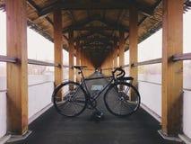 bicyclette Gris-noire de fixie dans le chemin en bois Photo stock