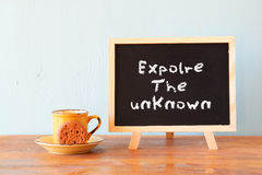 Blackboard with the phrase explore the unknown next to cup of coffee and cookie Royalty Free Stock Image
