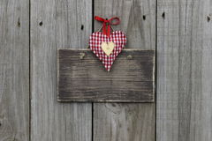 Blank wooden sign with red gingham and gold hearts hanging on wood background Stock Photo