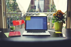 Blogger needs workstation, workplace with open laptop, smartphone, notebook and pot of flowers Royalty Free Stock Images