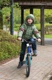 Blond boy enjoying bicycle ride Royalty Free Stock Image
