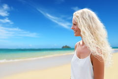 Blonde woman with long curly blond hair on beach Stock Photography