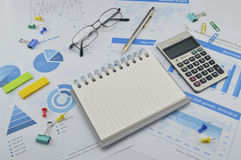 Book, pen, calculator, glasses on financial chart Royalty Free Stock Photo