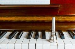 boquilla sobre las llaves del piano, cierre de la trompeta para arriba Fotos de archivo