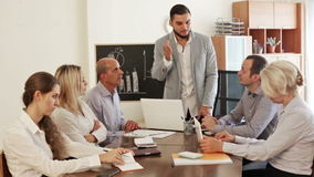 Boss and stressed co-workers on meeting indoors stock footage
