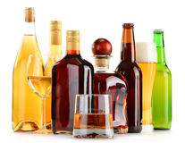 Bottles and glasses of assorted alcoholic beverages over white Stock Photography