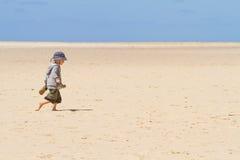 Boy child walking barefoot on sand Royalty Free Stock Photography