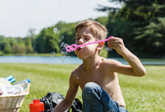 Boy enjoys blowing soap bubbles Royalty Free Stock Photos