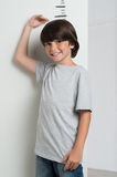 Boy growing tall and measuring himself Royalty Free Stock Images
